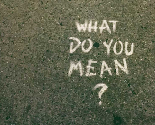 """Street sign with the words what do you mean? in reference to the Colombian word """"vaina"""""""
