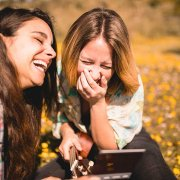 Two young women laughing about Colombian Spanish